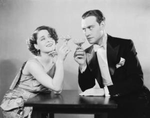 18th February 1930: Canadian actress Norma Shearer (1902 - 1983) shares a drink with a suspicious Conrad Nagel (1897 - 1970) in the film 'The Divorcee', directed by Robert Z Leonard. (Photo via John Kobal Foundation/Getty Images)